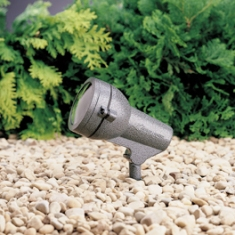 outdoor flood light in gravel with greenery in back